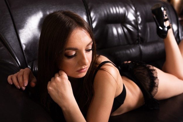A slender girl, in lingerie, lies on her stomach, on a black leather sofa. for any purpose.