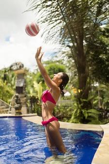 Стройная девушка-модель в сексуальном розовом купальнике играет в мяч в тропическом бассейне в джунглях.