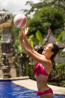 Slender girl model in a sexy pink swimsuit plays ball in a tropical pool in the jungle