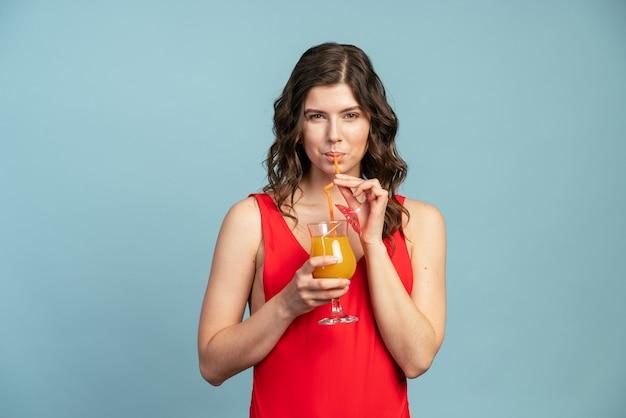 青い背景のほっそりした女の子は青い壁の背景にオレンジジュースを飲みます