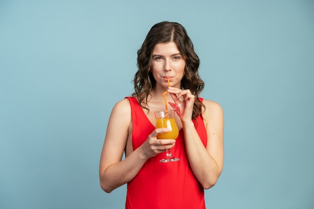 青い背景のほっそりした女の子はオレンジジュースを飲みます