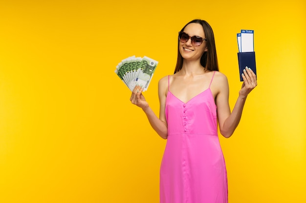 Slender girl in a pink dress and sunglasses holding passport with air ticket and hundred euro bills