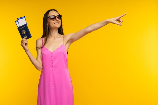 Slender girl in a pink dress and sunglasses holding passport with air ticket and pointing