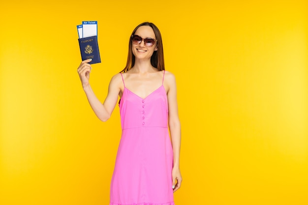 Slender girl in a pink dress and sunglasses holding passport with air ticket on a yellow background