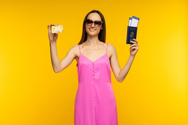 Slender girl in a pink dress and sunglasses holding passport with air ticket