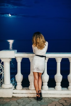 Slender girl in a white dress stands with her back on pier at the sea at night