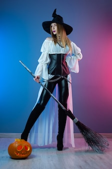 Slender girl in a witch costume for halloween with a broom and a pumpkin