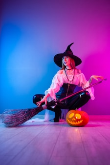 The slender girl in a witch costume for halloween with a broom and a pumpkin