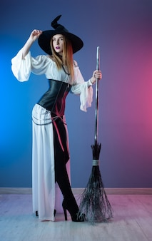 Slender girl in a witch costume for halloween with a broom
