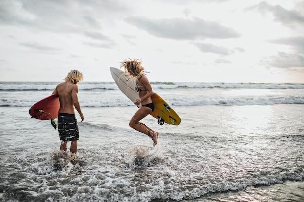 Ragazzo e ragazza snelli saltano in acqua di mare e tengono le tavole da surf