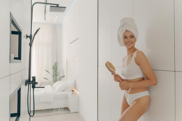 Стройная счастливая женская модель позирует с головой, завернутой в полотенце, прислонившись к стене ванной и держа деревянную щетку, готовясь к утреннему душу и гигиене. женская красота и уход за телом