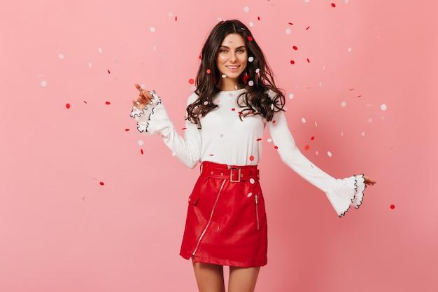 Стройная дама в прекрасном настроении танцует на розовом фоне с конфетти. девушка в кожаной юбке с улыбкой позирует.
