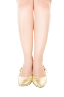 Slender legs gold shoes isolated.