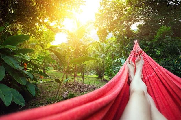 Стройные ножки девушки, лежащей в гамаке в тропических джунглях бразилии. бразилия