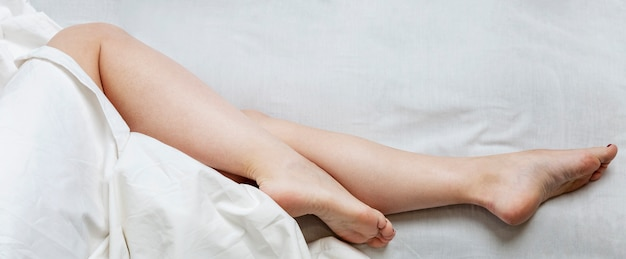 Slender legs of a sleeping woman on the bed. full sleep and relaxation.