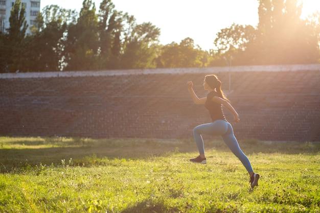 トレーニング中にジャンプするスポーツアパレルの細いモデルアスリート。テキスト用のスペース