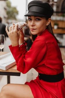 La modella snella non riusciva a trattenersi davanti a un delizioso croissant dolce, seduto in un caffè parigino. ritratto di giovane donna in rosso all'aperto