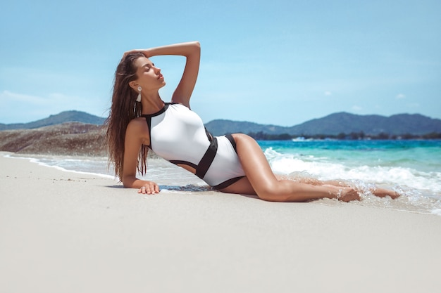 A slender model in a white swimsuit lies and sunbathes beach
