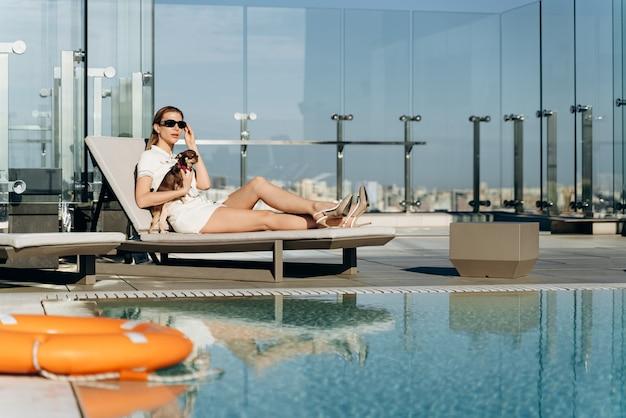 プールのそばで休んでいる彼女の腕の中に犬を持つ細身の、現代的な女の子。美しいブロンドは休んでいます