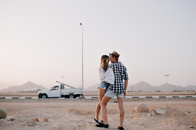 Стройная симпатичная женщина в винтажной белой рубашке хочет поцеловать своего парня, стоя на цыпочках под серым небом. красивая влюбленная пара обнимается перед машиной и наслаждается прекрасным видом на природу вечером