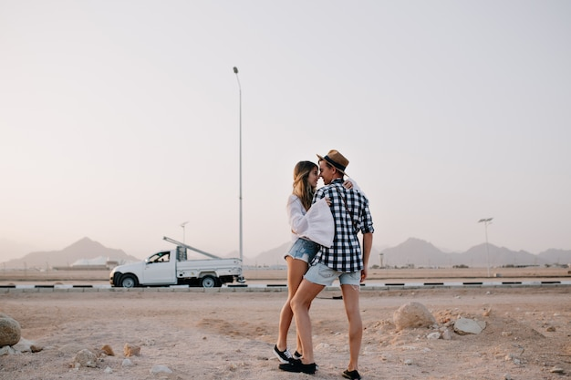 Slender pretty woman in vintage white shirt wants to kiss her boyfriend, standing on tiptoe under gray sky. beautiful loving couple hugging in front of car and enjoys amazing nature views in evening