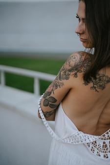 날씬한 섹시한 여자가 하얀 드레스를 입고 서서 매끈한 모습을 보이고, 어깨 너머로 보입니다.