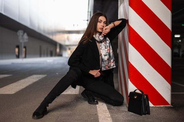 スタイリッシュな革の黒いハンドバッグとシルクの春のスカーフでファッショナブルなエレガントな服を着た細身のセクシーな若い女性は、駐車場の縞模様の柱の近くで休んでいます。屋外で魅力的な女の子のファッションモデル