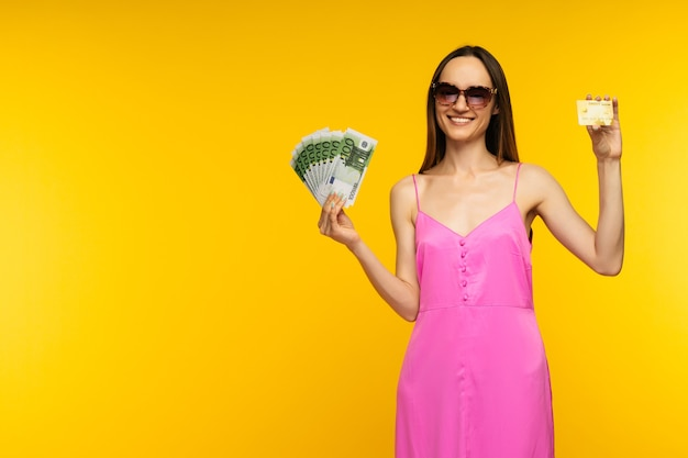 Slender spanish girl in a pink dress and sunglasses holding a hundred euro bills and a credit card