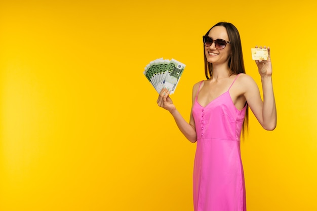 Slender spanish girl in a pink dress and sunglasses holding a hundred euro bills