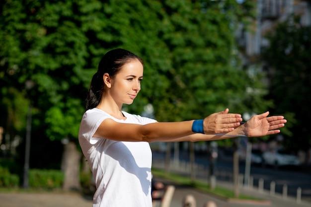 朝に青い輪ゴムで彼女の手のトレーニングをしているほっそりしたスポーティーな女の子