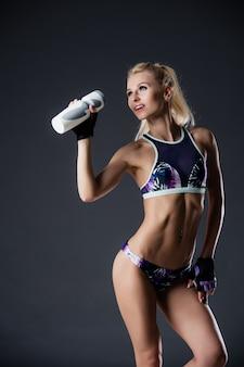ほっそりしたスポーティな女の子飲料水、フィットネス運動後休んで、疲れて、コピースペース