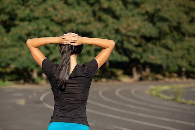 날씬한 스포티한 여성이 경기장에서 달리기 전에 스트레칭을 합니다. 태양 광선으로 야외 촬영입니다. 복사 공간