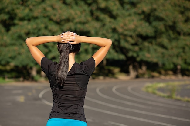 Slender sporty woman stretching before running at the stadium. outdoor shot with sun rays. copy space