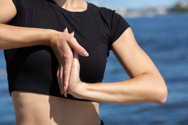 ビーチで手を伸ばすスポーツtシャツを着た細身の日焼けモデル。テキスト用のスペース
