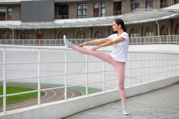 Slender tanned sporty girl stretching before running leaning her leg on barrier. space for text