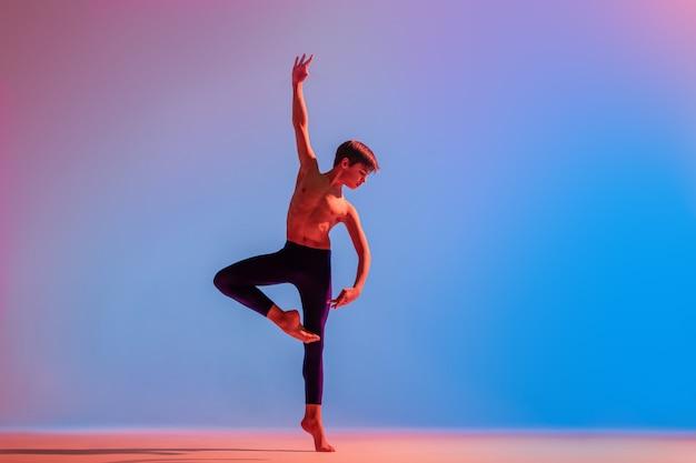 ほっそりした10代のバレエ少年ダンサーが色とりどりの光の下で裸足で踊ります。