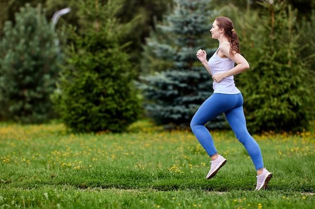Стройная белая женщина бежит на улице днем