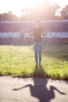 Стройная женщина-спортсменка в спортивной одежде делает тренировку со скакалкой на закате