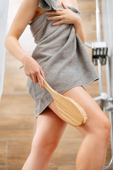 Slender woman in a gray towel in bathroom is engaged in body skin care anticellulite massage brush