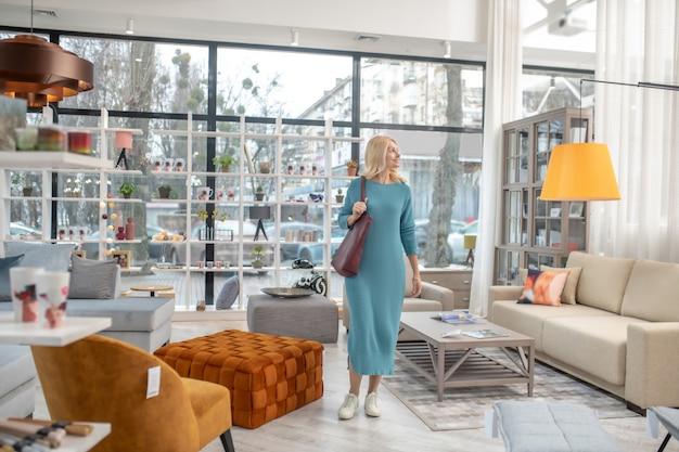 長いドレスを着た細身の女性と家具スタジオに立っているモカシン、黄色のランプの横を向いて喜んでいる。