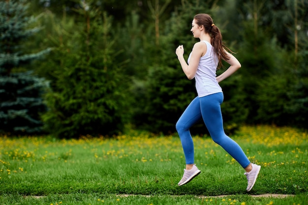 Стройная женщина в спортивной одежде бежит в городском саду