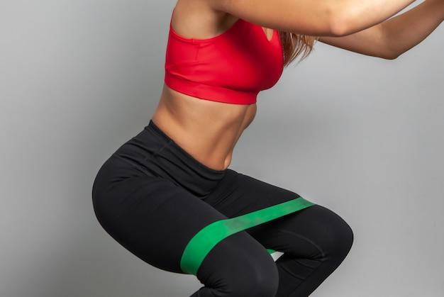 Стройная женщина в спортивной одежде с фитнес-резинками на сером фоне.