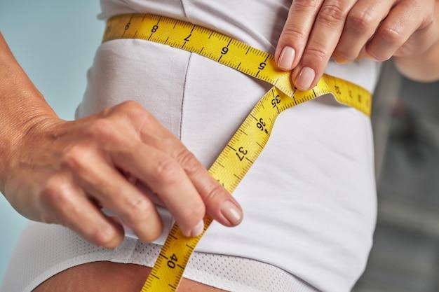 ウエストラインを測定する白いランジェリーの細い女性