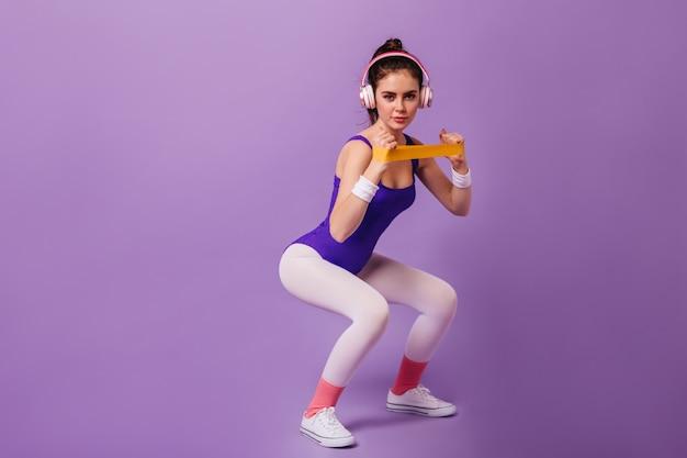Стройная женщина занимается спортом на фиолетовой стене