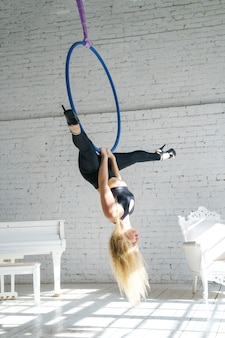 Slender woman is engaged in aerial gymnastics with a circle