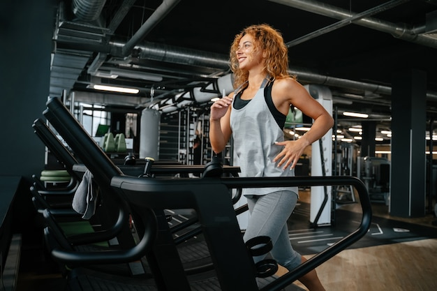 Slender woman jogging on a treadmill in an indoor gym is engaged in fitness concept of a healthy lif...