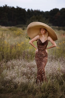 Slender woman in a long dress with leopard print and hat