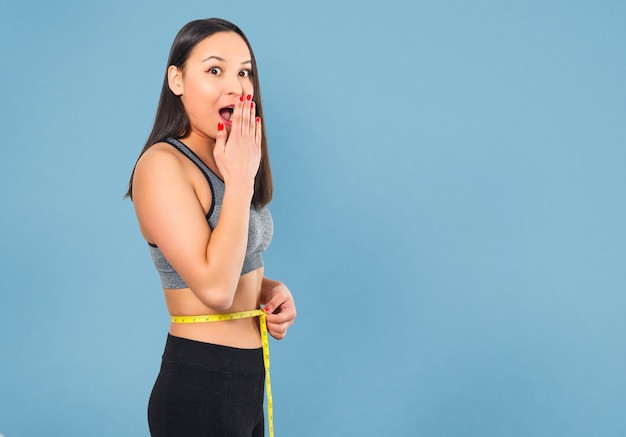 A slender woman measures her waist with a measuring tape. against a blue background.
