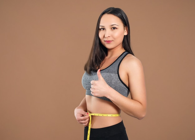 A slender woman measures her waist with a measuring tape. against a brown background.