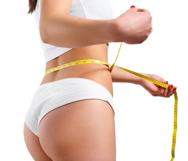A slender woman measures her waist with a measuring tape. against a white background.